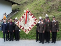 Stolz präsentieren die Funktionäre die renovierte Fahne